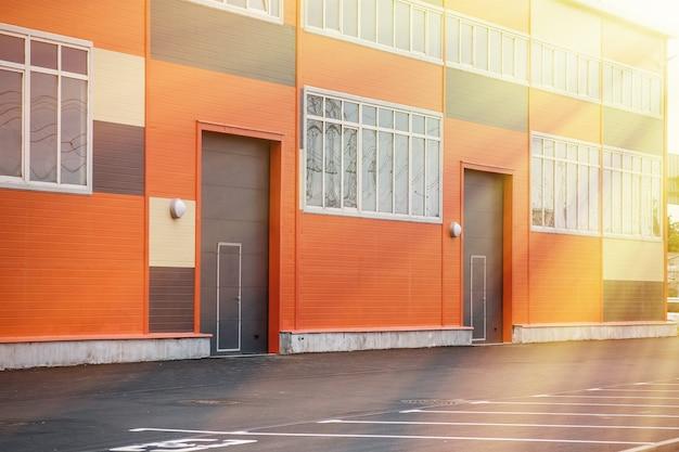 トラックに入るためのリフティングゲートを備えた倉庫の建物。