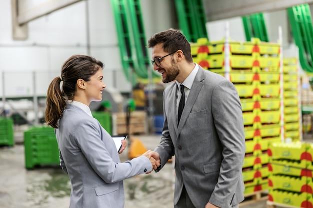 Складской бизнес. мужчина и женщина в деловом костюме обмениваются рукопожатием и завершают работу по транспорту и логистике. деловая женщина и бизнесмен на работе. успешно завершенный бизнес
