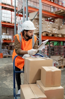 Инженер склада с тележкой просматривает список товаров