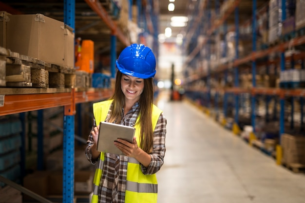 Warehouse female worker checking inventory on digital tablet in large distribution warehouse storage area