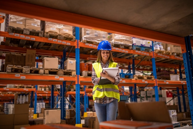 Warehouse female worker checking inventory in distribution warehouse