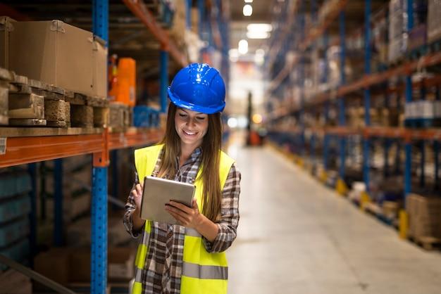 Работница склада проверяет инвентарь на цифровом планшете в большой складской зоне хранения