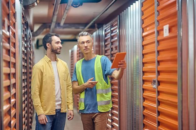 창고, 차고. 가장 가까운 차고 번호를 가리키는 태블릿으로 제복을 입은 웃고 있는 젊은 성인 수염 쇼핑객과 창고 직원