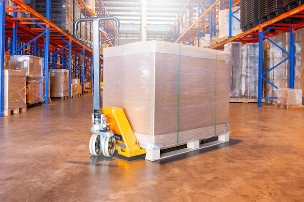 Warehouse interior with hand pallet truck and the shipment pallet.