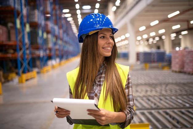 Управляющий складскими запасами держит контрольный список и смотрит в сторону