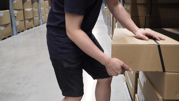 流通用の大規模な保管またはロジスティックまたは貨物を倉庫に保管します。そして男の手が箱を拾っています。