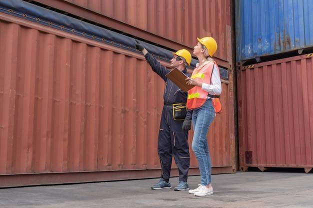 창고 물류 직원이화물 컨테이너 선적시화물 화물선에서 선적 컨테이너 상자를 배치하고 제품을 확인합니다.