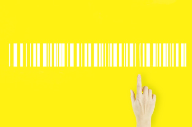 Warehouse and logistics concept. young woman's hand pointing finger with hologram bar code price tag on yellow background. inventory logistics production concept.