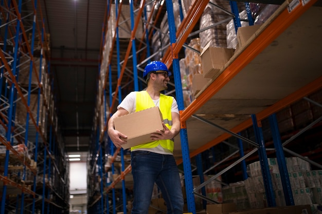 Warehouse male worker relocating packages and putting boxes on shelf in large storage distribution center.