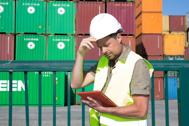 Warehouse man with safety equipment working check stock chart for logistic import export concept on warehouse
