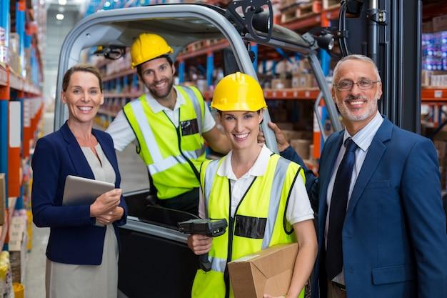 倉庫マネージャーと同僚と一緒に立っているクライアント