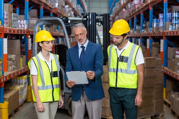 クリップボードを介して議論する倉庫マネージャーと同僚