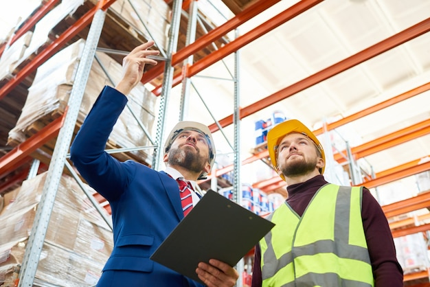 Warehouse manager giving instructions to worker