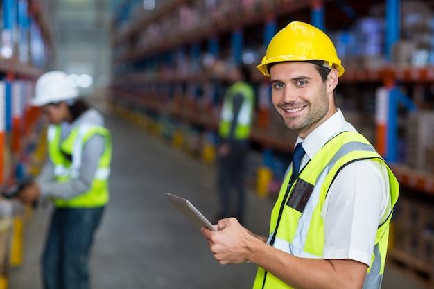 デジタルタブレットを保持している倉庫マネージャー