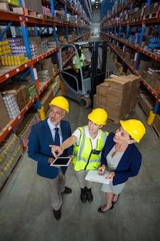 クライアントと女性労働者と対話する倉庫マネージャー