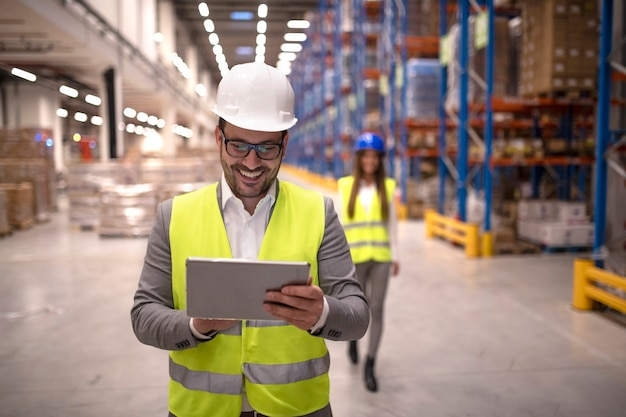 Warehouse manager reading report on tablet about successful delivery and distribution in warehouse logistics center