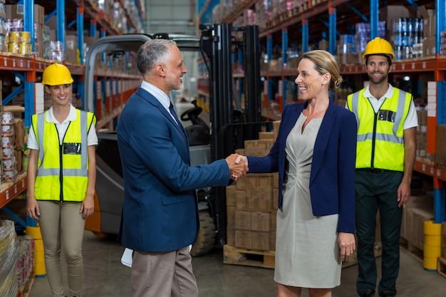 クライアントと握手する倉庫マネージャー