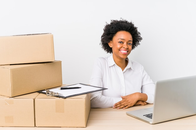 Warehouse manager sitting checking deliveries with laptop looks aside smiling, cheerful and pleasant.