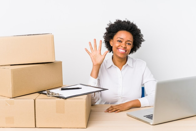 Warehouse manager sitting checking deliveries with laptop smiling cheerful showing number five with fingers.