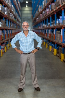 Warehouse manager standing with hands on hip