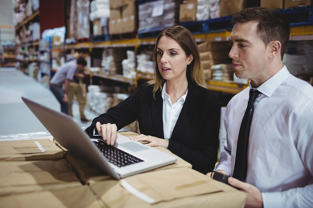 Warehouse managers using laptop in warehouse