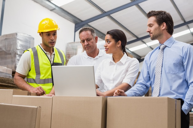 Warehouse managers and worker looking at laptop