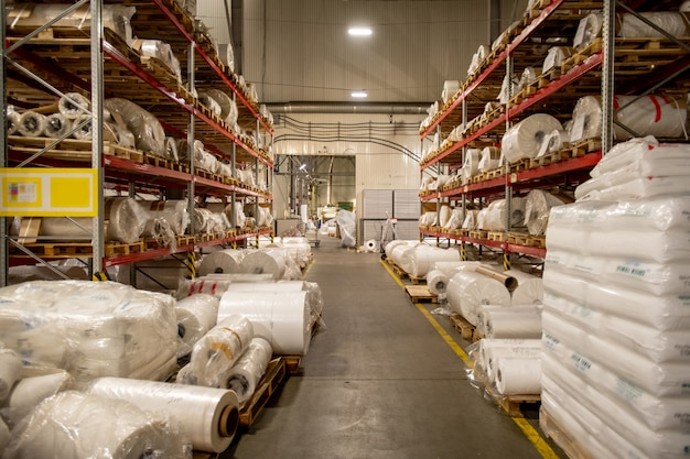 ポリエチレンフィルムのボビンを巻いて梱包したラックを備えた近代的な大規模化学生産工場の倉庫