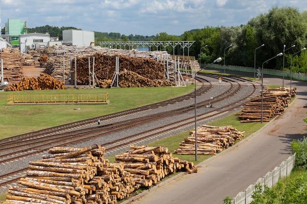 Склад древесного сырья под открытым небом на деревообрабатывающем заводе с подъездными железнодорожными путями