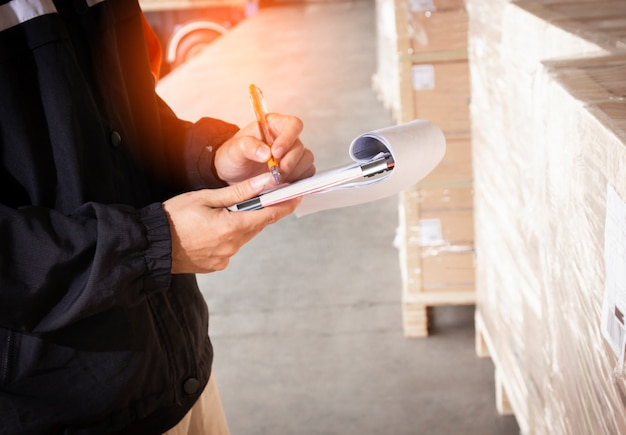 Warehouse staff are holding a clipboard with inventory the shipment pallet.