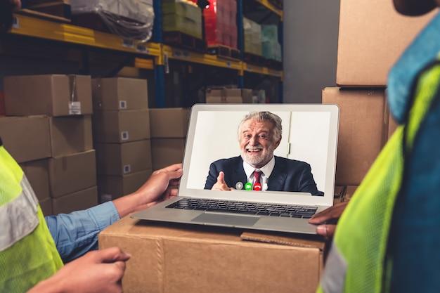 職場でビデオ通話について話している倉庫スタッフ