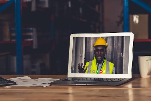 Персонал склада разговаривает по видеосвязи на экране компьютера на складе