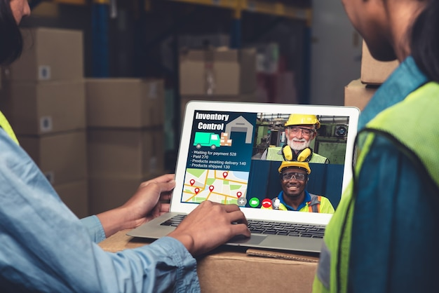 Warehouse staff talking on video call at computer screen in storage warehouse