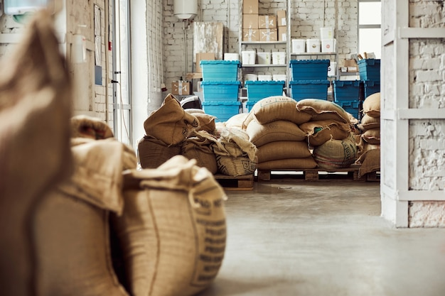 Warehouse with coffee beans packed in burlap sacks and blue containers
