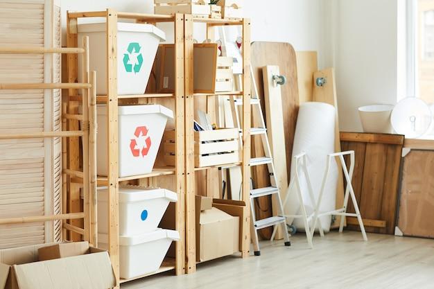 ゴミ箱やその他の物資が置かれた木製の棚がある倉庫