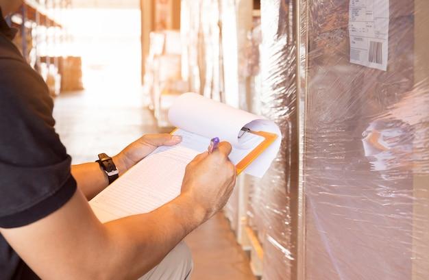 창고 작업자는 제품 재고와 함께 데이터 시트에 클립 보드 쓰기를 들고 있습니다.