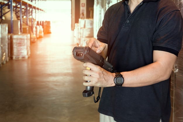 Warehouse worker are holding bar code scanner with inventory the products in warehouse.