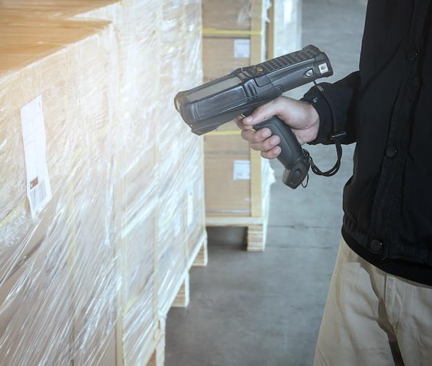 창고 작업자가 선적 팔레트에서 스캔하여 바코드 스캐너를 들고 있습니다.