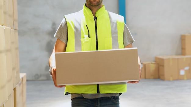 Работник склада, несущий картонную коробку на складе