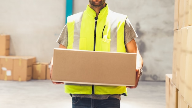 Warehouse worker carrying cardboard box in the warehouse