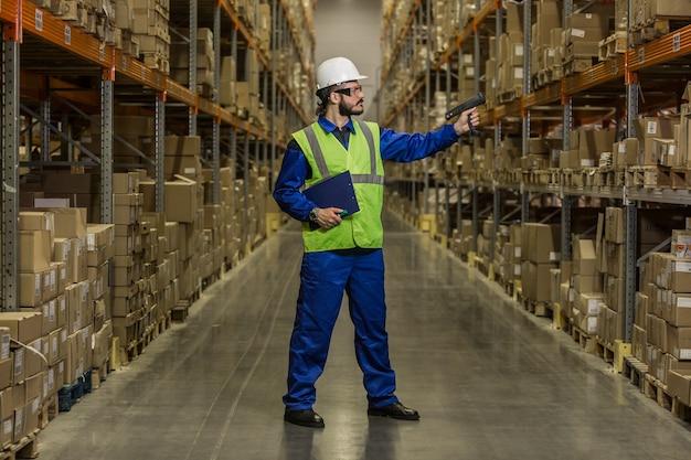 Работник склада, проверяющий груз на полках с помощью сканера
