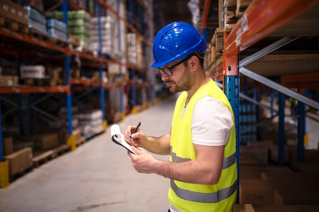 Warehouse worker checking inventory in large distribution center