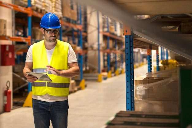 Работник склада проверяет инвентарь на цифровом планшете на большом складе.