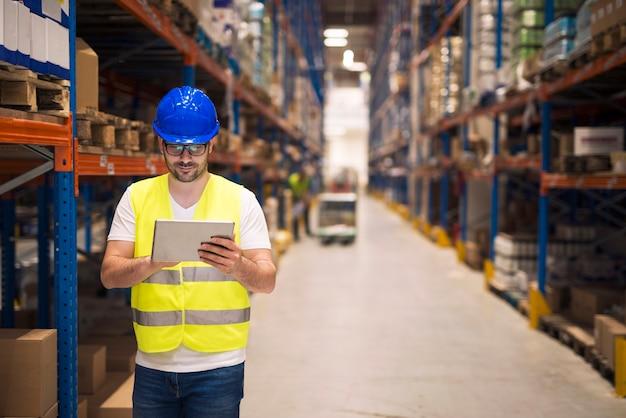 Работник склада проверяет инвентарь на своем планшете во время прогулки по большому складскому помещению с полками и упаковками на заднем плане