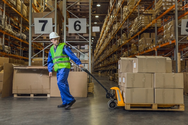 Работник склада тащит тележку с товарами