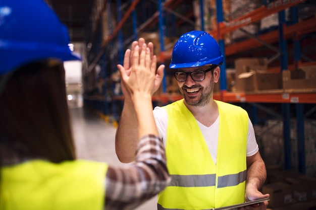 Warehouse worker giving high five to his friend colleague
