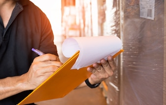 Warehouse worker hand holding clipboard with checking inventory of products