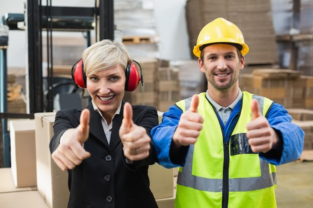 Warehouse worker and his manager giving thumbs up Premium Photo