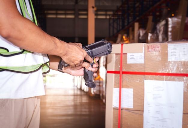 Работник склада, держащий сканер штрих-кода, проверяет продукты. компьютерные инструменты для управления складскими запасами.