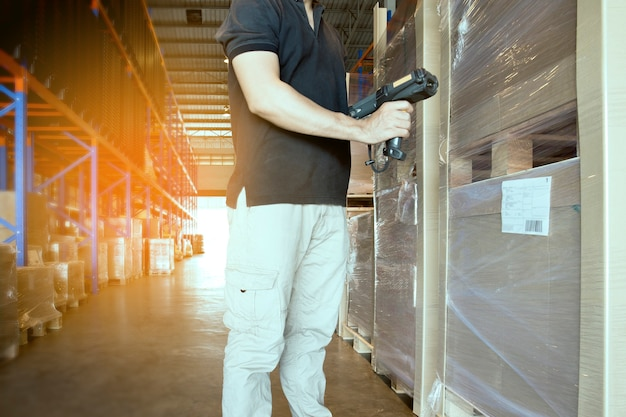 Warehouse worker holding barcode scanner with checking of product pallet.