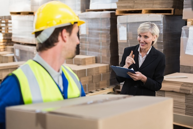 Warehouse worker holding box with manager behind him